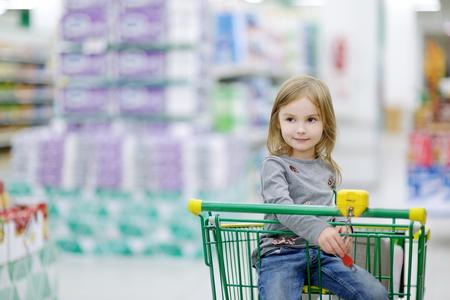 niños de compras: Niña adorable que se sienta en carro de compras Foto de archivo