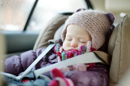 americana: Niño niña dulce durmiendo pacíficamente en un asiento de seguridad en el invierno