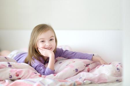 Little preschooler girl in pajamas on sunny morning Stock Photo