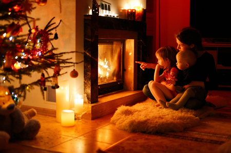 family in living room: Young mother and her daughters by a fireplace on Christmas