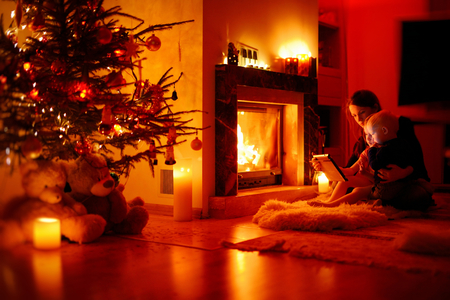 Young mother and her daughters using a tablet pc by a fireplace photo
