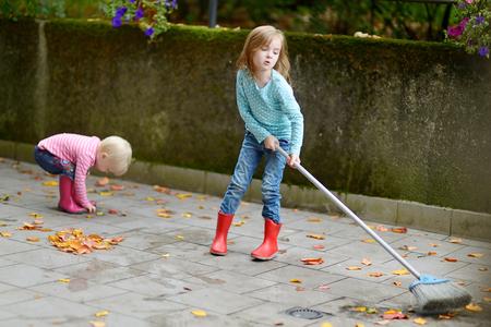 cute little girls: Ni�as lindas que barren las hojas amarillas secas en d�a de oto�o Foto de archivo