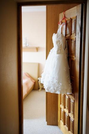 c�r�monie mariage: robe de mari�e courte accroch� une porte
