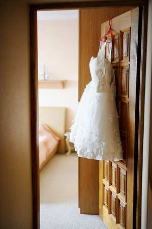 bride dress: Short wedding dress hanging on a door