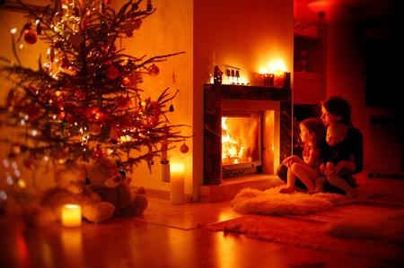 bambini pensierosi: Giovane madre e le sue figlie da parte di un camino a Natale