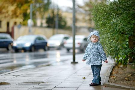 rainy season: Adorable toddler girl at rainy day in autumn