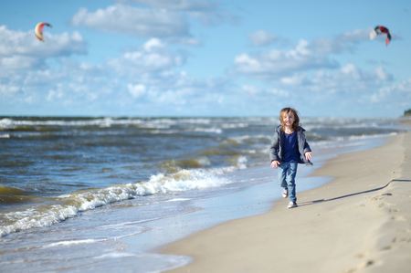 teen beach: Adorable little girl running and laughing on the beach