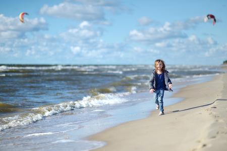 playa vacaciones: Adorable ni�a corriendo y riendo en la playa Foto de archivo