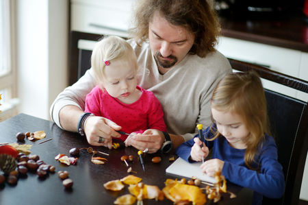 creatures: Father and his kids making chestnuts creatures together