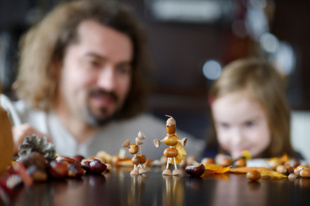 creatures: Father and his kid making chestnuts creatures together