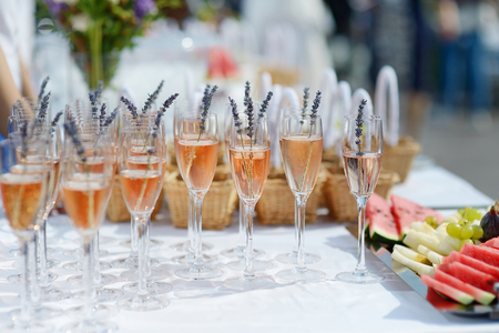 pink wedding: Glasses of with pink champagne decorated with lavender