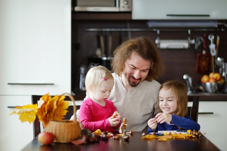 conkers: Father and his kids making chestnuts creatures together