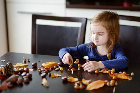 cr�atures: Adorable little girl making chestnuts creatures