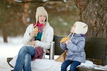 picnicking: Mother and her daughter picnicking in the park at winter