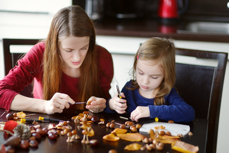 cr�atures: Mother and her kid making chestnuts creatures together Banque d'images