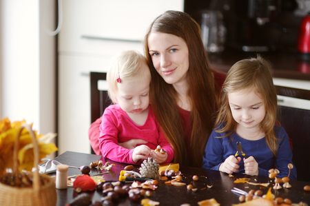 cr�atures: Mother and her kids making chestnuts creatures together