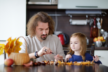 conkers: Father and his kid making chestnuts creatures together