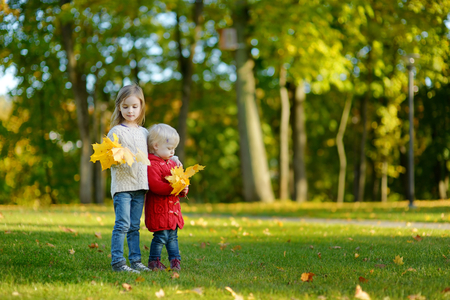 september 2: Two little sisters having fun in beautiful autumn park