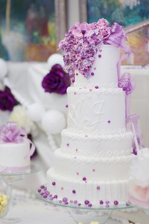 pastel boda: Pastel de boda blanco decorado con flores de color púrpura de azúcar