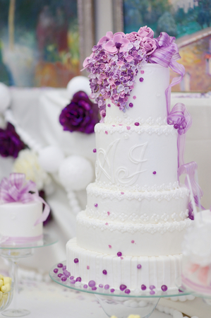 wedding table decor: White wedding cake decorated with sugar purple flowers