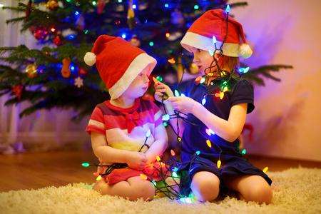 Dos pequeñas hermanas que adornan el árbol de Navidad Foto de archivo