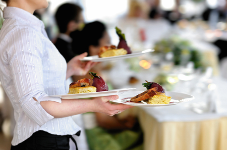 waitresses: Waitress carrying three plates with meat dish