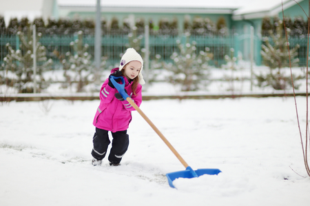 shoveling: A young girl takes pride in completing a big shoveling job