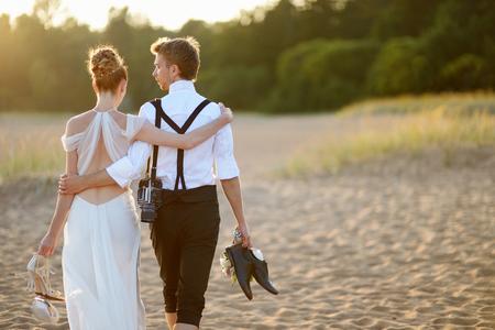 Gelukkige bruid en bruidegom op een mooi strand op zonsondergang