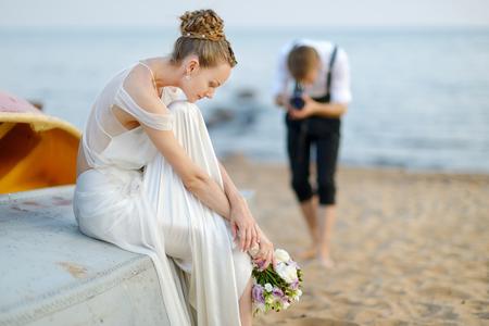 Stellen van de bruid op haar bruidegom tijdens het fotograferen met een oude camera Stockfoto