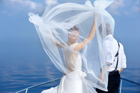 travel destination: Happy bride and groom hugging on a yacht