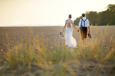 Lyckliga bruden och brudgummen på en vacker strand på solnedgången