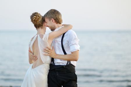 nude bride: Beach wedding: bride and groom hugging by the sea
