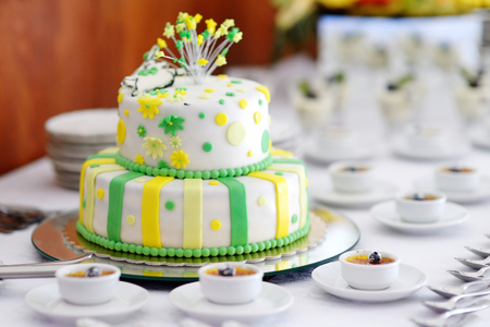 Striped wedding cake decorated with yellow and green flowers