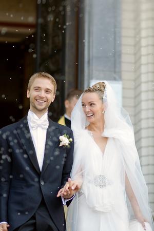 sotto la pioggia: Felice coppia appena sposata sotto una pioggia di riso