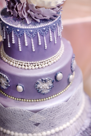 wedding table decor: Purple wedding cake decorated with flowers and pearls