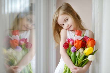 white day: Adorable smiling little girl with tulips by the window