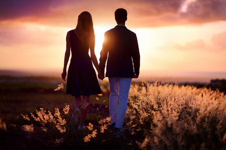 love silhouette: Young couple enjoying the sunset in the meadow