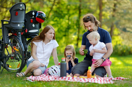 picnicking: Happy family of four picnicking in the park Stock Photo