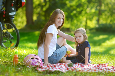 picnicking: Young mother and her daughter picnicking in the park Stock Photo