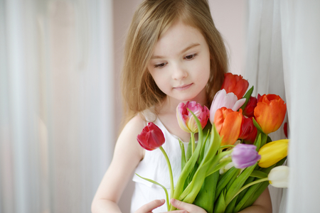 day dream: Adorable smiling little girl with tulips by the window