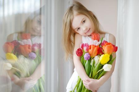 Schattige lachende meisje met tulpen door het raam Stockfoto - 40753735