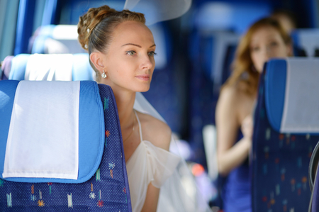 Beautiful young bride portrait in a wedding bus