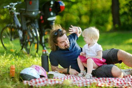 picnicking: Young father and his daughter picnicking in the park