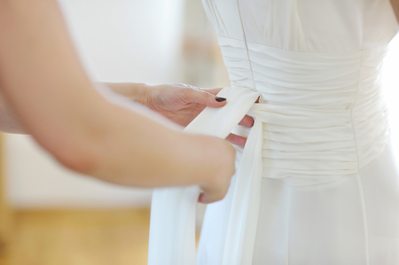 bridal dress: Helping the bride to put her wedding dress on Stock Photo