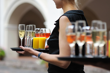skoal: Waiter with dish of champagne, wine and juice glasses Stock Photo