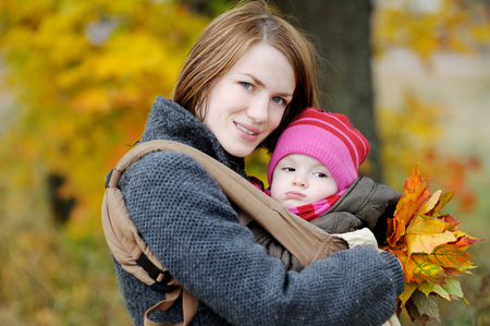 Young mother and her little baby in a carrier photo