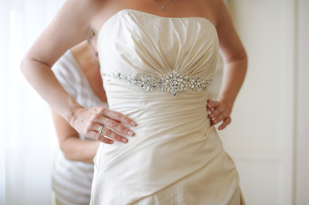 Putting beautiful wedding dress on
