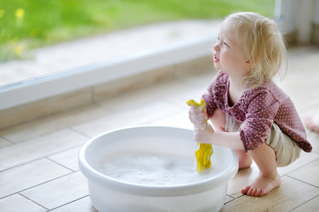 clean home: Little toddler girl helping her mom to clean up