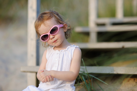 Adorable toddler girl sitting on the stairs by the sea photo