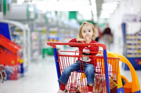 Muchacha adorable del niño que se sienta en la cesta de la compra